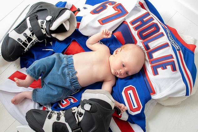 baby posing on ice hockey kit