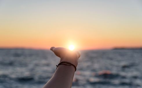 Female hand reaches for the sun at sunset against the background of the sea.jpg