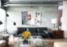 Studio blu inc, black sofa, Hide rug, Concrete walls, glass coffee table, green vintage lamp