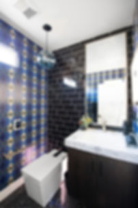 blue wall paper, black subway tile, modern toilet, blue glass light, polished nickel custom mirror,