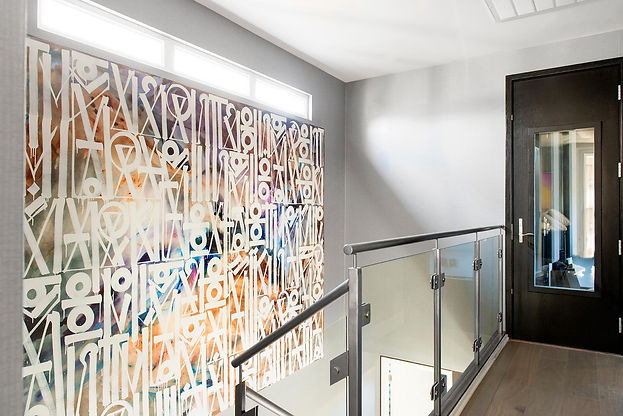 art on stairs, grey wall paper, glass railings