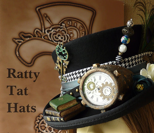 The Celebrant by Ratty Tat Hats, an inky black, low crown lady's hat with verdigris mono-goggle and stack of miniature leath