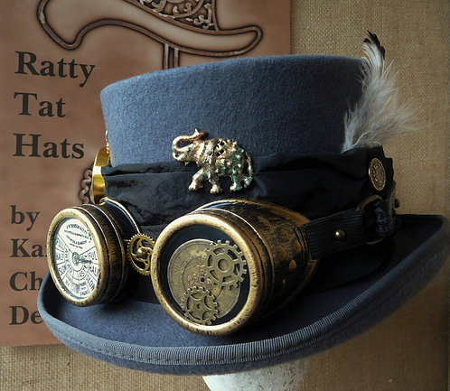 Phileas Fogg, a dark grey Steampunk hat with goggles, compass and enamelled elephant