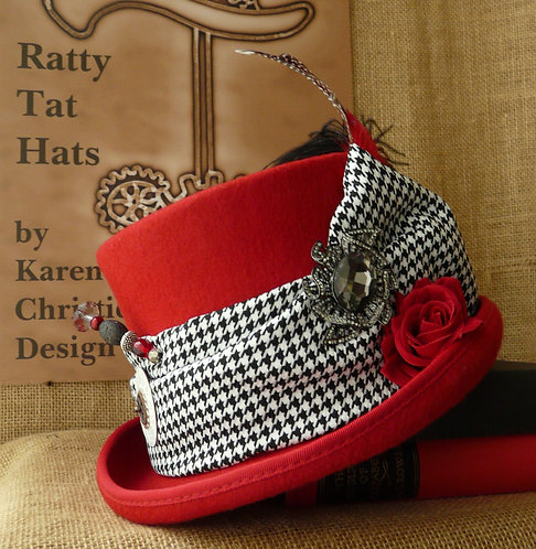Scarlet red top hat with black and white dogstooth fabric, pocket watch parts and hatpin
