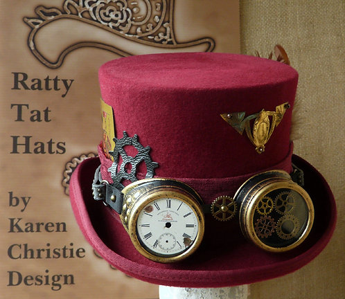 A burgundy Steampunk hat with goggles leather and metal cogs and watch and clock parts