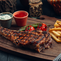 Grilled beef steak with fries, grilled tomato, pepper and sauces