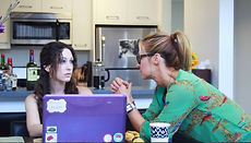 Two women talk in a kitchen. One has a laptop. The other has her hands up in front of her.