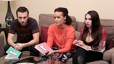 Three people sit on a couch holding notebooks in a therapy session