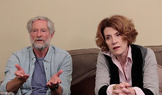 An older man and woman sit on a couch looking concerned