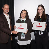 A man presenting awards to Shannan Leigh Reeve and Chelese Belmont for Cinespace.