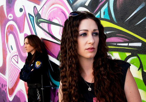 Two women against a grafittied wall. One is a cop and the other looks off out of frame
