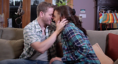 A man and a woman kiss on a couch in their living room.