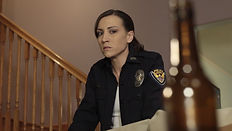 A woman in a police uniform stares at a beer bottle in her home.