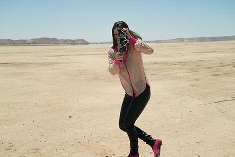 Chelese Belmont holding a camera to her eye in the desert.