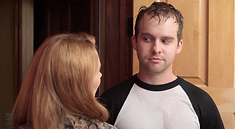 A man with wet hair and clothes looks mischievously at a woman whose back is to the camera.