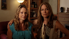 A woman has her arm around another woman in her living room as they look concerned