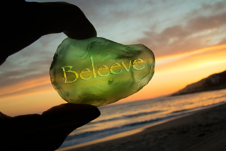 Two fingers hold a green rock with the word Beleeve. Beach at sunset in Background