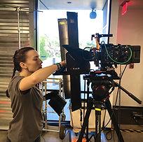 A Woman setting up a camera