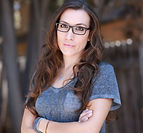 Shannan Leigh Reeve wearing glasses and crossing her arms, smiling at the camera.