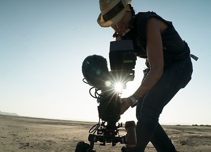 Shannan Leigh Reeve holding a camera with the sun peaking through behind her in the desert.