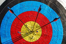 A target with black, blue, red, and yellow circles. Four arrows stick out of the middle.