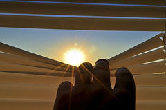 A hand pulling down blinds to reveal a shining sun