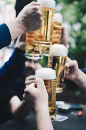 hands holding full beer glasses