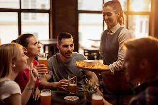 Group of happy friends drinking beer in