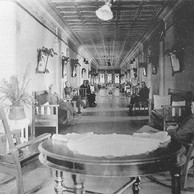 This circa 1920's male wing hallway includes rooms on both sides and a parlor with triple windows seen at the far end of the hallway.