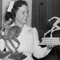 Miss Mary Elwell, occupational therpist, admires wood figures of an equestrian and a sprinter carved out of wood by an inmate at Metropolitan State Hospital. 1941 © John Gray