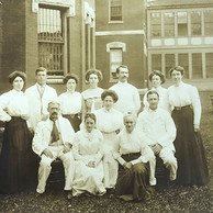 A group of male and female attendants pose in this circa 1900 photo, while a patient peers out of a window behind them.