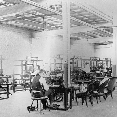 Occupational therapy was carried out on a large scale. Here, workers are at numerous looms, while in the foreground a  patient works a sewing machine in the upholstery work area.
