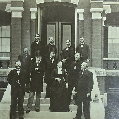 Five hospital Trustees and administrative staff, including Dr. Julia K. Casey, stand on the steps of the Central Administrative Buildingin this 1880s formal photograph.