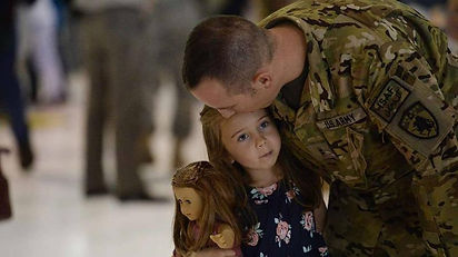 Daniel Millington of Company G, 2nd Battalion, 135th Aviation Regiment shares a quiet moment with his daughter Samantha, 5, as he returns from Afghanistan after 10-month deployment in 2014. GETTY IMAGES
