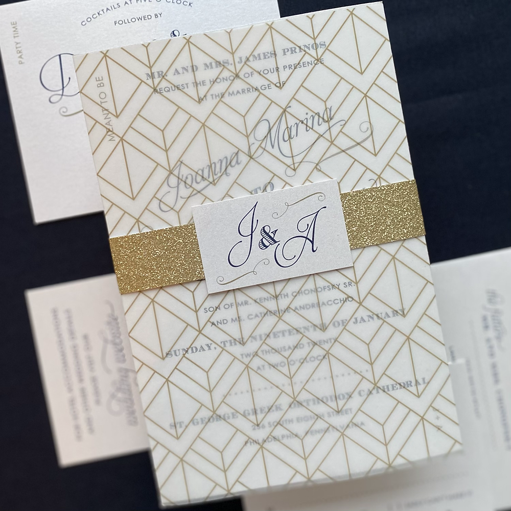 Wedding invitation in a sheer deco patterned wrap with a gold glitter band