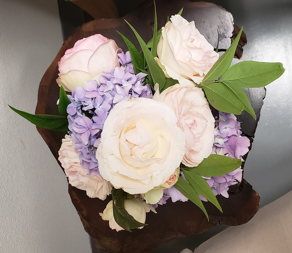 A small, special order arrangement using pink garden roses, lavender hydrangea and nandina.