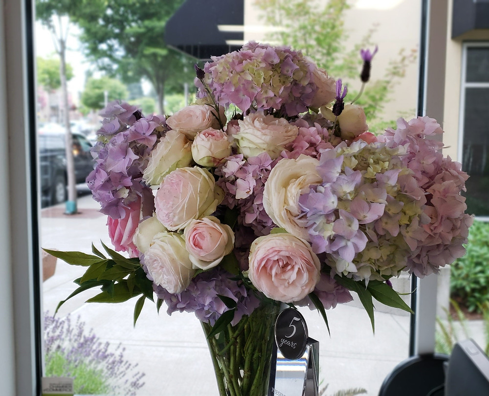 A weekly bouquet subscription using pink garden roses, lavender hydrangea, lavender and nandina.