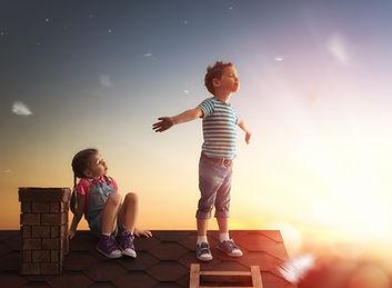 Kleine Kinder sitzen auf dem Dach
