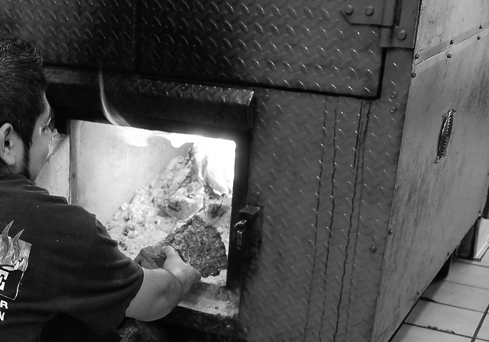 Man loading wood into a wood-burning meat smoker