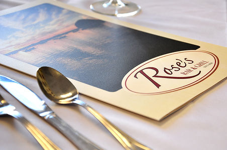 Rose's laminated menu on a white table cloth, wine glass in the background, silverware in the foreground