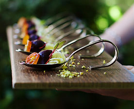 Appetizers lined up on a wood tray
