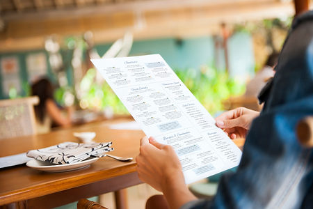 Woman holding a restaurant menu while seated at a table