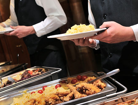 Servers serving food at a buffet table