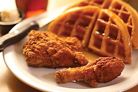 3 pieces of crispy fried chicken and a waffle with syrup