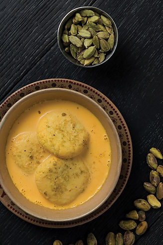 A bowl of Ras Malai, soft poached cheesecake patties in mango-flavored milk, topped with chopped pistachios