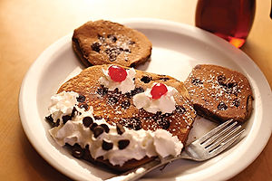 Mickey-shaped buttermilk pancake with chocolate chips and face made of whipped cream and cherries