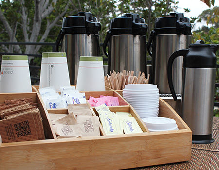 Catered coffee pots with cups, lids, sugars, cream, stirrers and cup sleeves