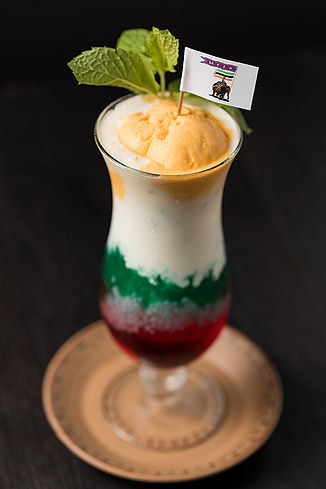 A hurrican glass fill with Faluda, a layered ice cream, syrup and jelly dessert drink