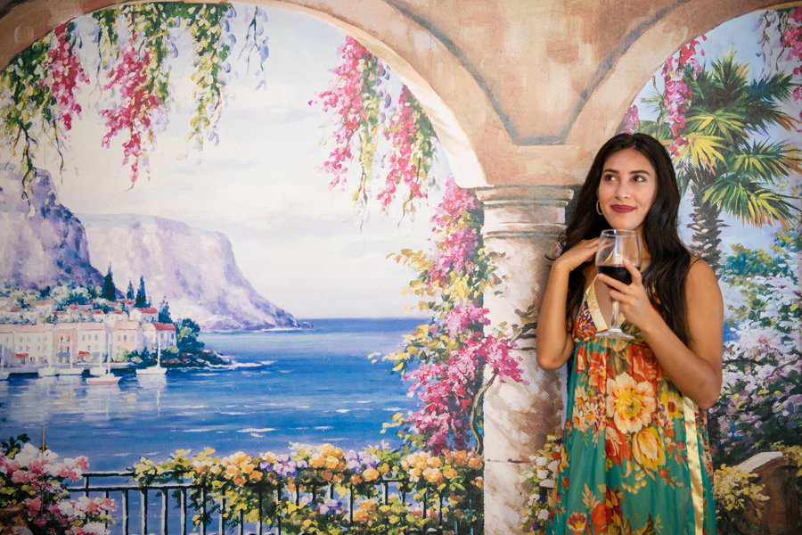 Woman with glass of red wine standing in front of a mural of an Italian seaside view