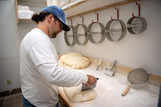Guy Slicing Large Pizza Dough into Smaller Portions